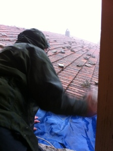 Chris attempting to put a tarpaulin on the roof in the rain...