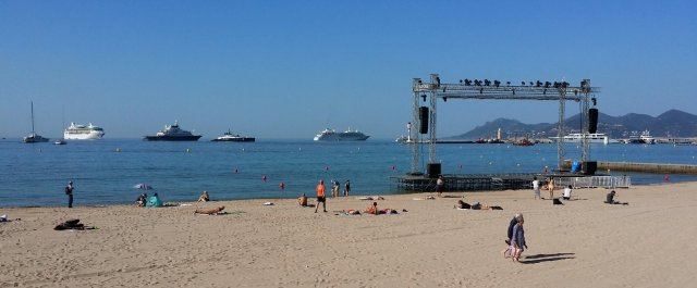 The public beach transformed with an open-air screen, backed by yachts and a cruise liner