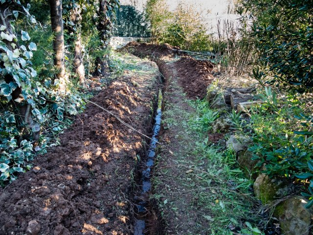 shows the new trench with water in it from the old broken pipe